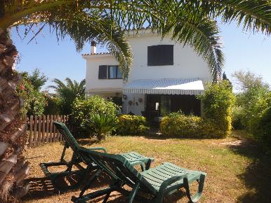 Unter einer Palme stehend geht der Blick über den mediterranen Garten auf die Ferienhäuser La Carina und La Casilla